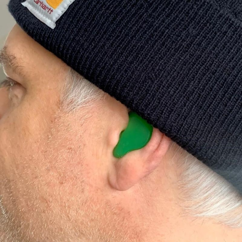 Picture of man wearing custom molded ear defeenders for industrial strenght hearing protection-min